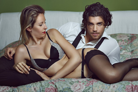 sexual intimacy: Fashion couple relaxing on bed. Man looks camera Stock Photo