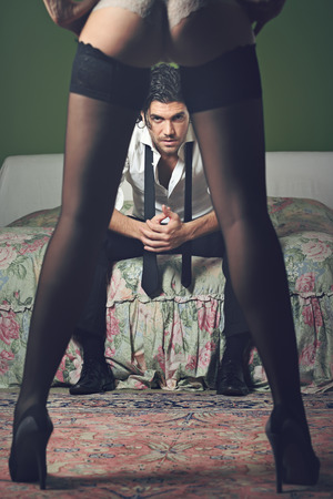 human leg: Elegant man portrait with sensual woman legs as foreground . Stock Photo