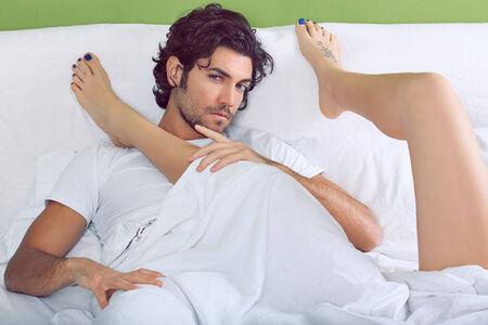 piernas hombre: Retrato divertido del hombre hermoso en la cama blanca rodeada de piernas de la mujer Foto de archivo