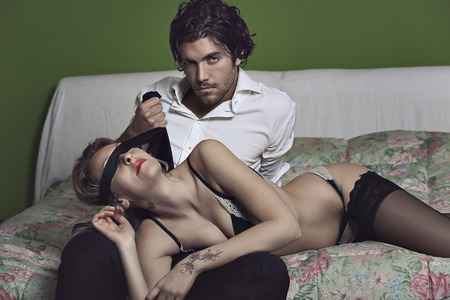 beds: Dark fashion man covering woman eyes with a black tie . Passion and seduction concept