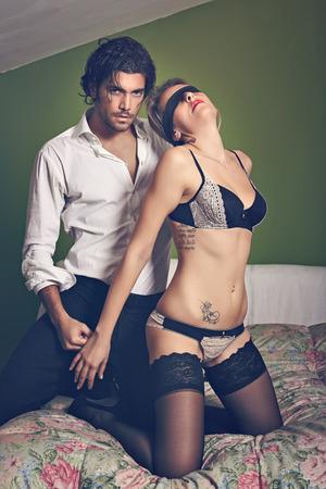 Hombre hermoso con la mujer con los ojos vendados en ropa interior. La seducción y pasión concepto