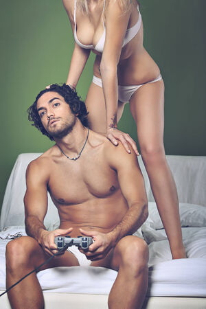 sexy couple in bed: Sexy woman angry with her video game addicted man . Funny sexy couple