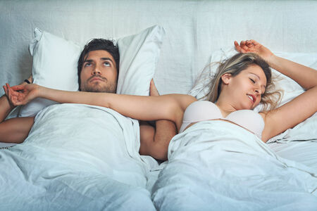 Man with funny expression has problem with woman snoring