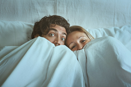Frightened couple with eyes wide open under the sheets Stock fotó