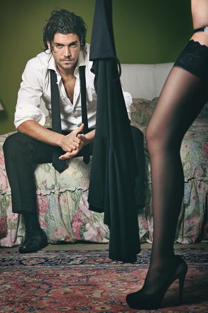Handsome elegant man seated on bed . Fashion posing photo