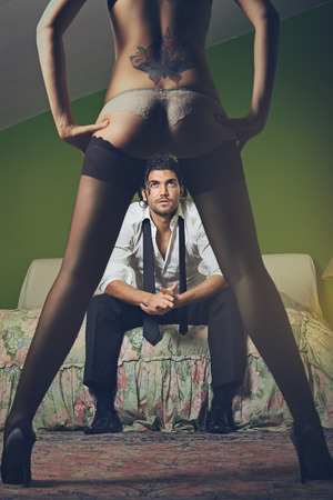 boudoir: Fashion man looks at woman with sensual legs . Seduction and passion concept Stock Photo