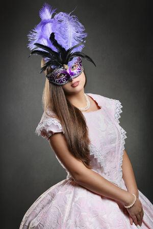 velvet dress: Beautiful woman in pink historical dress with purple venetian mask . Venice carnival portrait