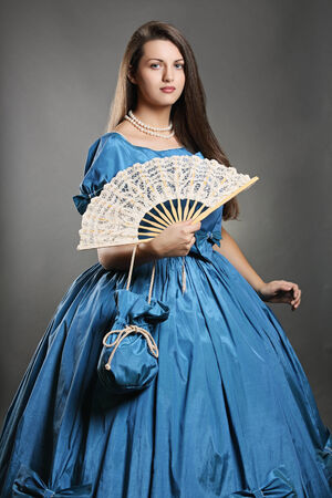 Noble pose of a beautiful woman wearing blue elegant costume with fan  . Venice carnival Banco de Imagens