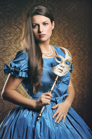 Beautiful woman in blue historical dress with venetian mask . Venice carnival portrait Banco de Imagens