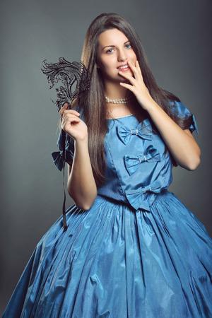 velvet dress: Beautiful woman in blue princess dress with black mask . Venice carnival portrait