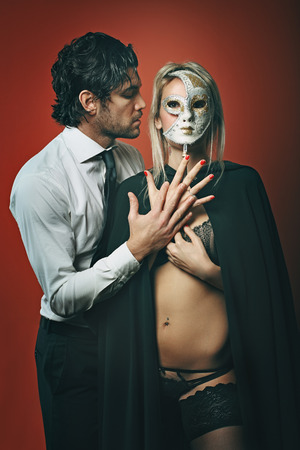 Elegant fashion man with beautiful woman wearing a venetian mask . Sensuality conceptual photo