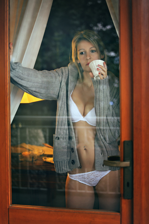 boudoir: Beautiful woman looks outside the window with cup of coffee in hand Stock Photo