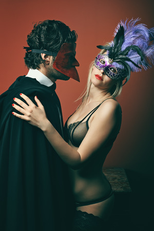 masquerade masks: Fashion couple wearing venetian masks. Venice masquerade and carnival Stock Photo