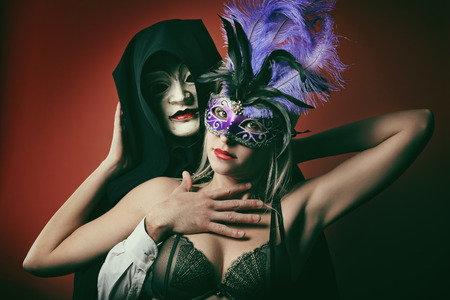 masquerade costumes: Portrait of a fashion couple with masks . Venice carnival and party