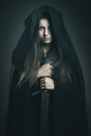 robe: Beautiful dark woman with black robe and sword . Fantasy and legend Stock Photo