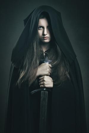 Mooie donkere vrouw met zwart gewaad en zwaard. Fantasie en legende Stockfoto