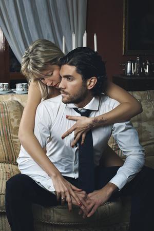 Beautiful fashion woman undressing elegant man. Saint Valentine day celebration