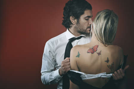 seduction: Handsome fashion man undressing woman . Seduction and passion