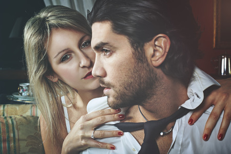 woman undressing: Intense gaze from beautiful woman undressing man. Love and celebration concept