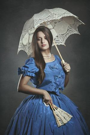 美しい女性の高貴な傘とファンでポーズします。ヴェネツィアのカーニバル 写真素材