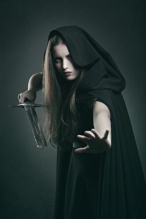 Mooie donkere vrouw met zwaard in het bestrijden van positie. Fantasie en legende