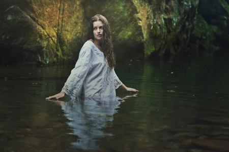 Mooie vrouw in een donkere magische stroom. Fantasie en surrealistische begrip Stockfoto