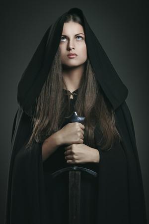 黒マントと剣と美しい女性。ファンタジーと伝説 写真素材