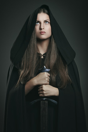 Beautiful woman with black cloak and sword . Fantasy and legend