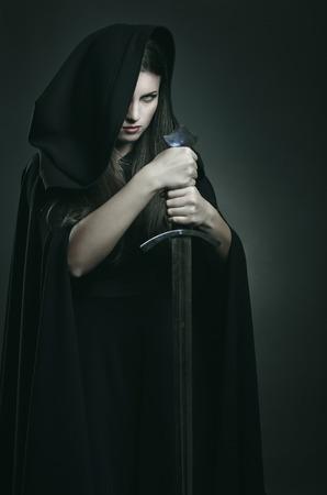 Evil uitdrukking van mooie donkere vrouw met een zwaard. Fantasie en legende