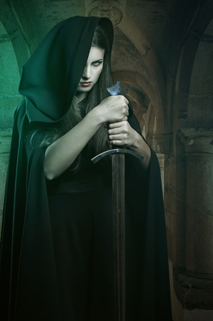 Beautiful woman with sword in a stone castle. Fantasy and legend