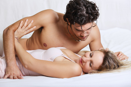 closeness: Beautiful woman refusing intimacy with her man in bed . Couple problems concept Stock Photo