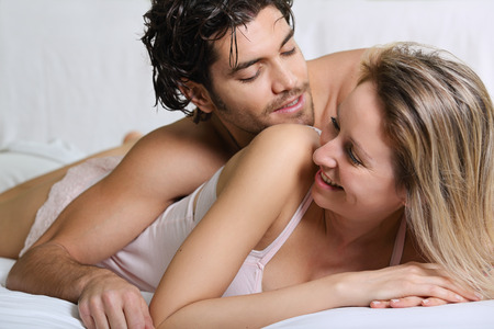 Joyful couple smiling and happy in bed . White and fresh portrait