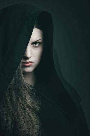 黒いローブを持つ美しい女性の肖像画を暗い。ハロウィーンと恐怖の概念