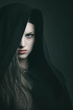 Dark portrait of a beautiful woman with black robe . Halloween and horror concept