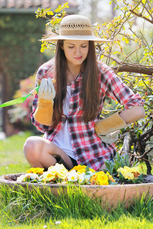 indecision: Beautiful young woman with indecision expression looks at flowers. Garden concept