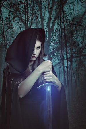 Mooie vrouw met magisch zwaard in een donker bos. Fantasie en legende