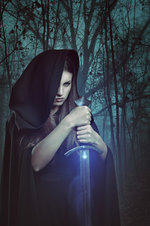Beautiful woman with magic sword in a dark forest. Fantasy and legend