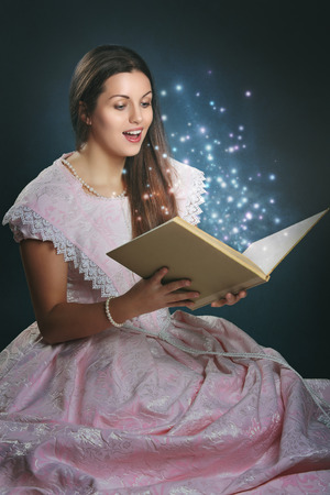 Beautiful woman dressed like a fairytale princess with magical book photo