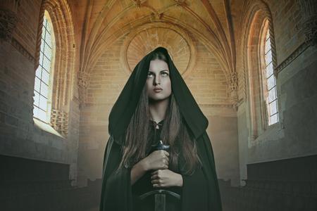 rycerz: Rycerz kobieta z średniowiecznego miecza. Kamienny zamek w tle