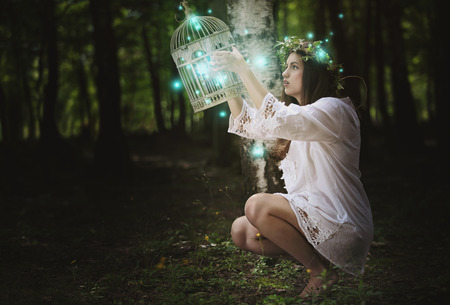 secrets: Beautiful young woman with ghost lights in secret forest . Fantasy concept Stock Photo