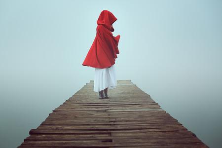 caperucita roja: Caperucita rojo oscuro en la niebla. Sueño y colores surrealistas
