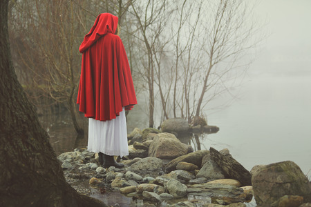 cape: Little red riding hood on a shore of a misty lake . Sadness and surreal concept Stock Photo