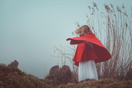 the little red riding hood: Retrato oscuro y surrealista de una mujer con capucha de color rojo. La tristeza y la soledad conceptual
