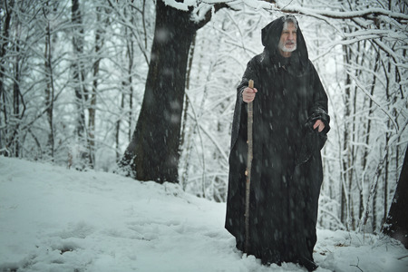 Old pilgrim with black robe in a snowy forest