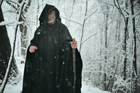 Old wizard in snowy forest . Fantasy and fairy tale Stock Photo