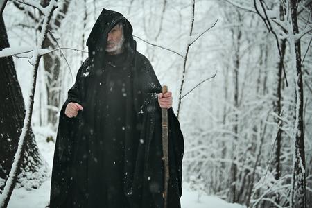 Oude tovenaar in besneeuwde bossen. Fantasie en sprookjes Stockfoto