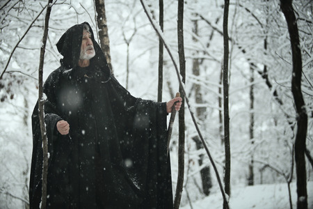 Old wise man in dark forest with snow . Fantasy and fairy tale