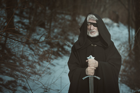 one eyed: Old one eyed man with sword in a dark forest . Fantasy and mythology Stock Photo