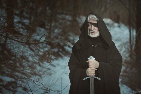 Oude eenogige man met zwaard in een donker bos. Fantasie en mythologie Stockfoto
