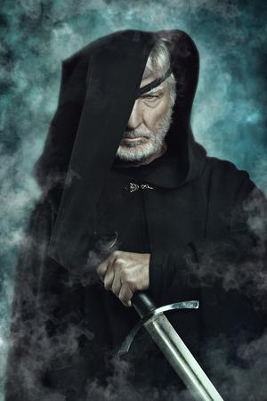 fantasy warrior: One eyed warrior with black cape and sword . Fantasy and mythology